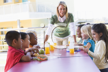 Royalty Free Photo of Students Eating Lunch and the Teacher at the Table