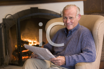 Royalty Free Photo of a Man Beside a Fireplace