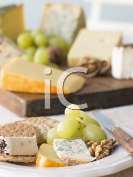 Royalty Free Photo of a Plate of Cheese and Biscuits with a Cheese Board