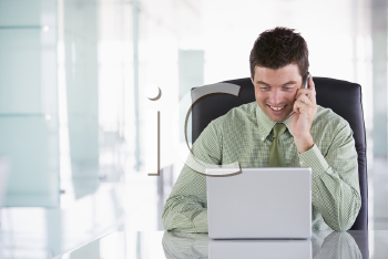 Royalty Free Photo of a Man With a Laptop Talking on the Phone