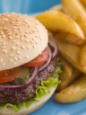 Royalty Free Photo of a Beefburger With Salad and Pickles in a Sesame Seed Bun With Chips