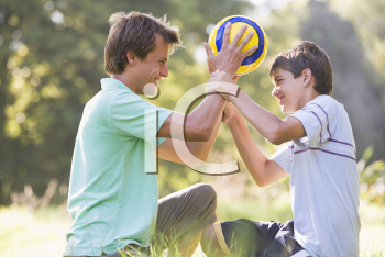 Royalty Free Photo of a Man and Boy With a Soccer Ball