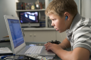 Royalty Free Photo of a Boy Listening to an MP3 Player While on a Laptop