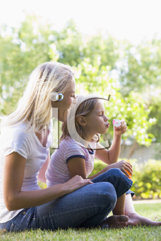 Royalty Free Photo of a Mother and Daughter Blowing Bubbles