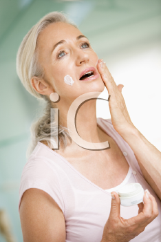 Royalty Free Photo of a Woman Applying Face Cream