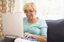 Royalty Free Photo of a Woman in a Living Room With a Laptop