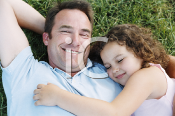 Royalty Free Photo of a Father and Daughter Asleep on the Lawn