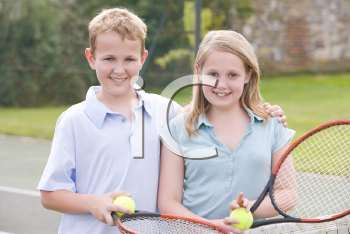 Royalty Free Photo of a Boy and Girl on a Tennis Court