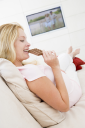 Royalty Free Photo of a Pregnant Woman Eating Chocolate in Front of the TV