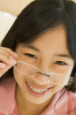 Royalty Free Photo of a Girl Looking Through Glasses