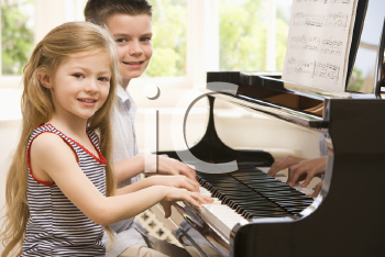 Royalty Free Photo of a Brother and Sister Playing Piano