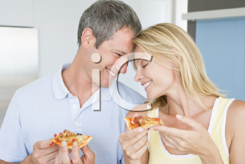 Royalty Free Photo of a Husband and Wife Eating Pizza
