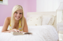 Royalty Free Photo of a Girl Reading in Her Room