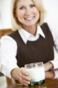 Royalty Free Photo of a Woman Reaching for a Glass of Milk