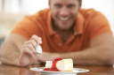 Royalty Free Photo of a Man Eating Cheesecake