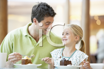 Royalty Free Photo of a Father and Daughter Having Cake at a Mall