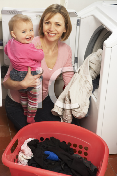 Royalty Free Photo of a Woman Doing Laundry With Her Baby