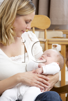 Royalty Free Photo of a Mother Holding a Baby in the Nursery