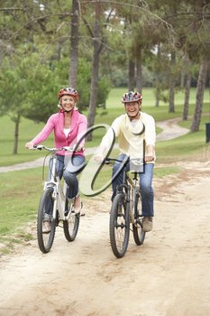 Senior couple riding bicycle in park