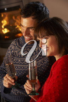 Middle Aged Couple Sitting Sofa By Cosy Log Fire With Glass Of Champagne