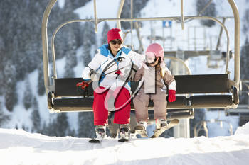 Mother And Daughter Getting Off chair Lift On Ski Holiday In Mountains