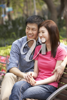 Young Chinese Couple Relaxing On Park Bench Together