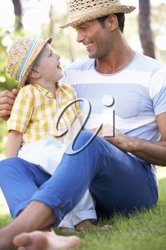 Father And Son Relaxing In Summer Garden