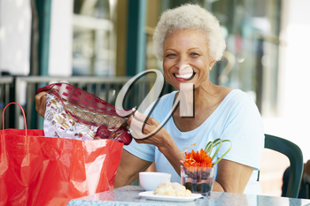 Senior Woman Enjoying Snack At Outdoor Caf� After Shopping