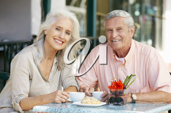 Senior Couple Enjoying Snack At Outdoor Caf�