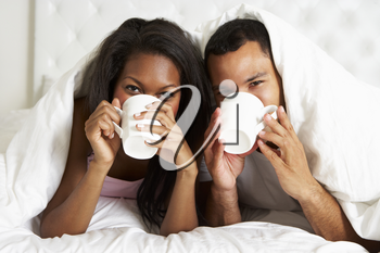 Couple Relaxing In Bed With Hot Drink