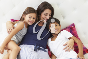 Mother And Children Relaxing In Bed Wearing Pajamas
