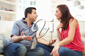 Hispanic Couple Sitting On Sofa Arguing
