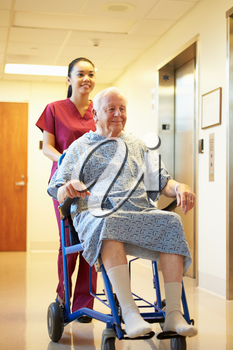 Senior Male Patient Being Pushed In Wheelchair By Nurse