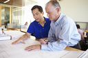Architects Studying Plans In Modern Office Together