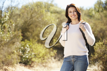 Portrait Of Woman Hiking In Countryside Wearing Backpack