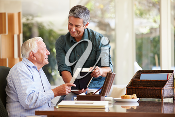 Senior Father Looking At Photo In Frame With Adult Son