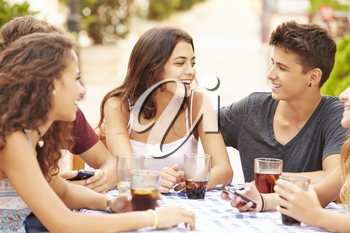 Group Of Teenage Friends Sitting Together At Caf�