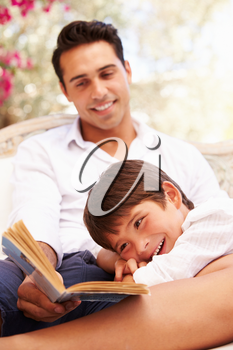 Father And Son Sitting In Garden Reading Book Together