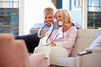 Mature Couple At Home In Lounge Using Digital Tablet
