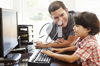Hispanic father and son using computer at home