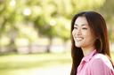 Head and shoulders portrait Asian woman outdoors