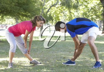 Senior Woman Working With Personal Trainer In Park