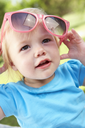 Female Toddler Trying To Put On Sunglasses