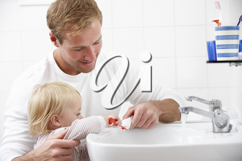 Father And Daughter In Bathroom Brushing Teeth