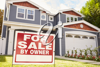 Large suburban house with �for sale� sign displayed outside
