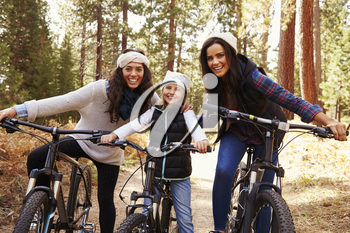 Female parents cycling with their daughter in a forest