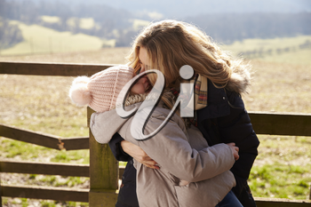 Mother kissing her daughter by a gate in the countryside