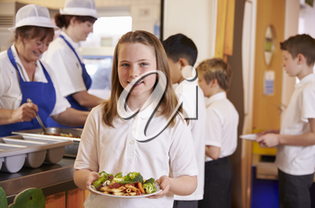 Schoolgirl holding a plate of food in a school cafeteria