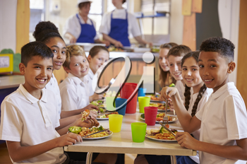 Kids at a table in a primary school cafeteria look to camera
