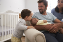 Family With Son And Newborn Brother In Nursery